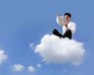 business man sitting on a cloud working with tablet pc
